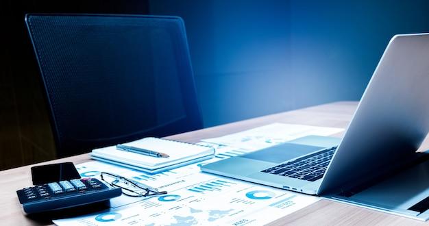 Calculadora, laptop e papelada na mesa da sala de reuniões