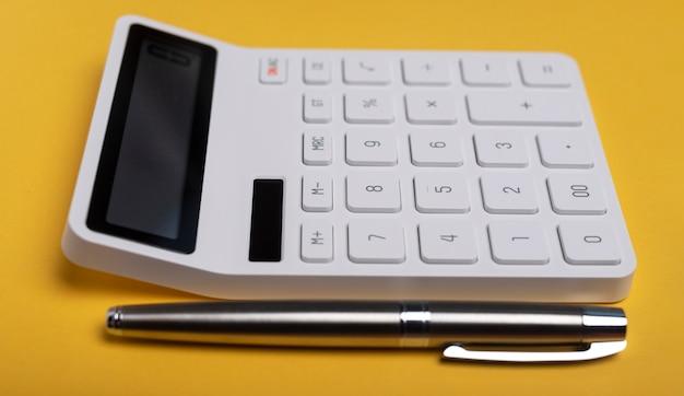 Calculadora na mesa amarela com caneta. local de trabalho do contador, vista lateral.