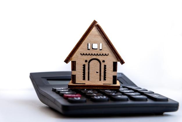 Calculadora na mesa com pequena casa. descreve o planejamento financeiro para investir ou comprar uma casa. planejamento de investimentos imobiliários, empréstimo à habitação, conceito de hipoteca.