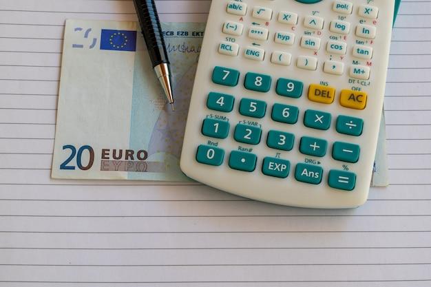 Calculadora, nota de vinte euros em folha de papel com lapiseira