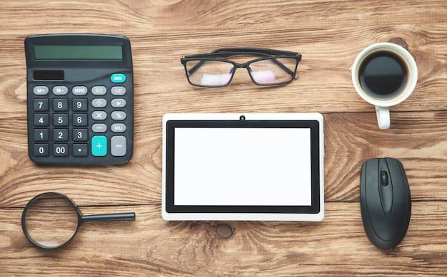 Calculadora, óculos, tablet, café em fundo de madeira.