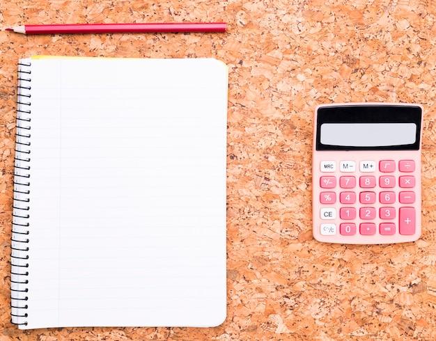 Calculadora perto de caderno e lápis