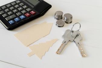 Calculadora; pilha de moedas; chaves com recorte de papel de casa e árvore na mesa de madeira branca