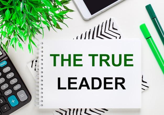 Calculadora, planta verde, telefone, marcador, caderno com o texto o verdadeiro líder na área de trabalho. postura plana.