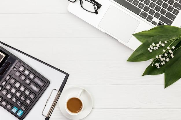 Calculadora, prancheta, xícara de café, óculos e laptop na mesa branca