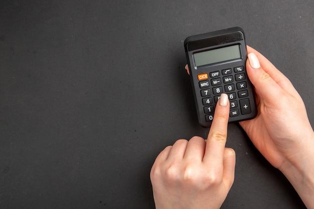 Calculadora preta com vista superior nas mãos femininas no espaço livre da mesa preta