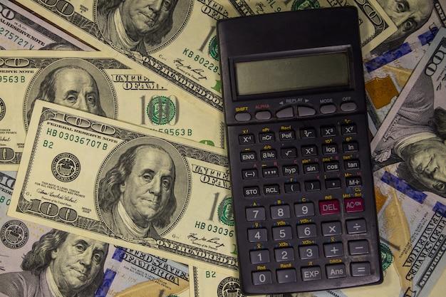 Calculadora preta sobre o fundo das notas de cem dólares americanas