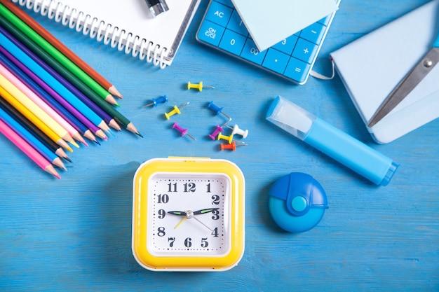 Calculadora, relógio, lápis, nota, marcador e notas adesivas no fundo azul