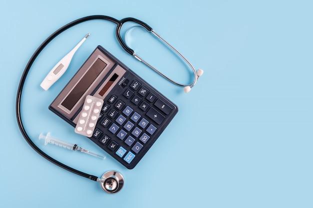 Calculadora, seringa, termômetro, pílulas e sthetoscope sobre fundo azul.