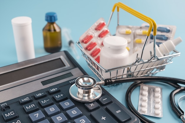 Calculadora, sthetoscope e cesto de compras com drogas de pilha sobre fundo azul.
