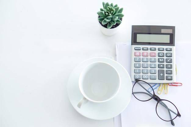 Calculadora, um copo vazio, óculos está pronto para o empresário usar