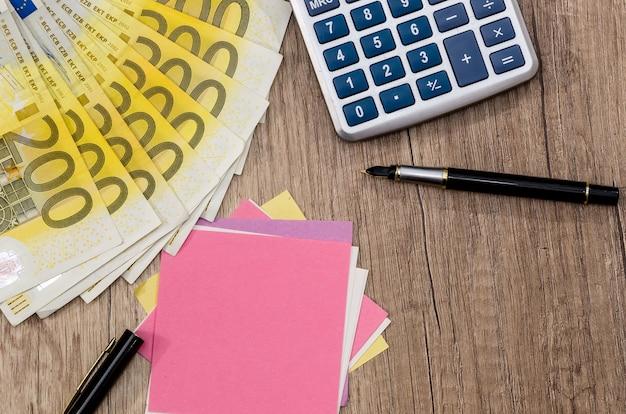 Calculadora wuth de 200 euros e caneta bloco de notas na mesa