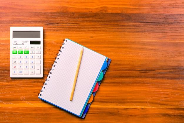 Calcular, caderno e lápis na mesa de madeira.