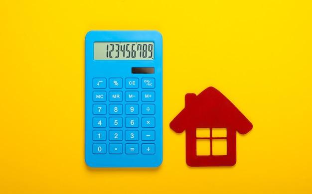 Cálculo do custo de aluguel de habitação. estatueta de casa vermelha, calculadora em fundo amarelo. vista do topo