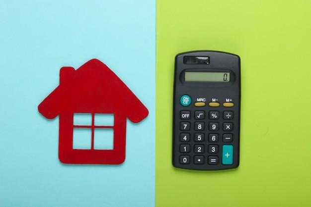 Cálculo do custo de aluguel de habitação. estatueta de casa vermelha, calculadora em um fundo azul esverdeado. vista do topo