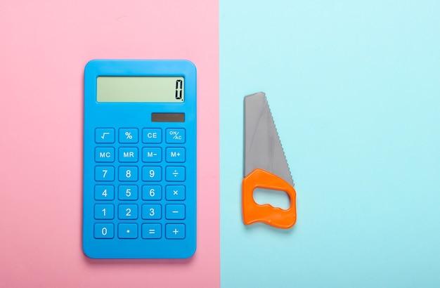 Cálculo do custo de construção de uma casa ou trabalho doméstico. calculadora e brinquedo viram em fundo azul-rosa pastel. vista do topo