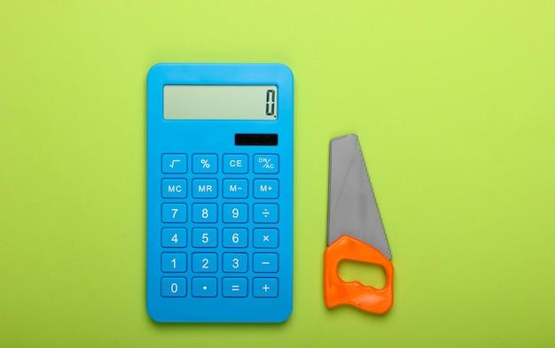 Cálculo do custo de construção de uma casa ou trabalho doméstico. calculadora e brinquedo viram sobre fundo verde. vista do topo
