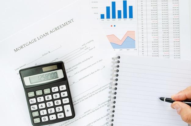 Cálculo dos pagamentos de um empréstimo hipotecário em uma imagem conceitual com calculadora, bloco de notas, caneta e planilhas