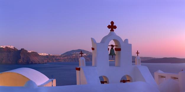 Caldeira vulcânica na ilha de santorini, sobre a torre do sino da igreja local em oia, santorini