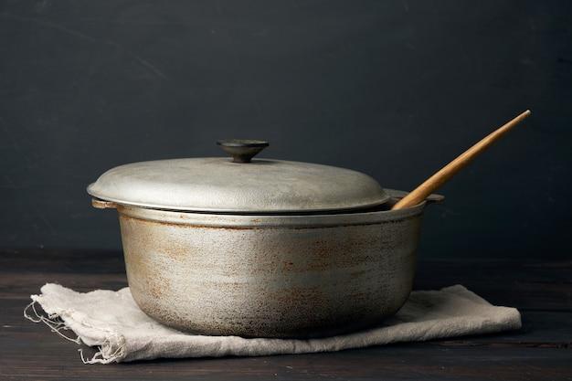 Caldeirão velho de alumínio sobre uma mesa de madeira, utensílios de cozinha