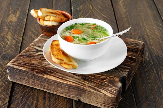 Caldo de frango com macarrão e fatias de cenoura em uma mesa de madeira em estilo rústico.