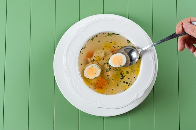 Caldo de galinha com carne, cenoura, ervas e ovo de codorna em um prato branco sobre uma mesa verde