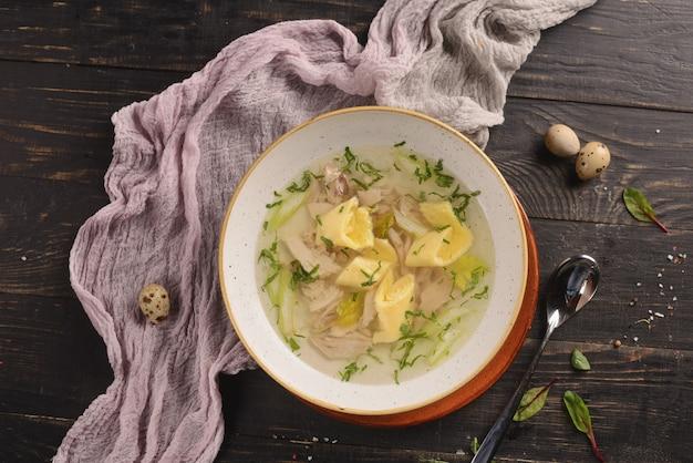 Caldo de galinha com carne, legumes e cebolinha. em um prato branco sobre uma mesa de madeira