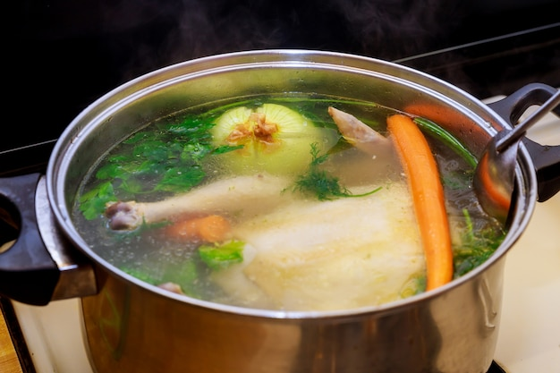 Caldo de galinha com cenoura, frango inteiro, cebola, aipo e salsa em panela de aço