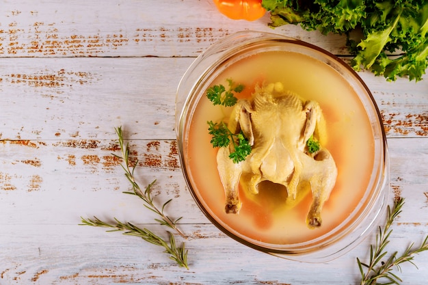 Caldo de galinha com cenoura, frango inteiro, cebola, aipo e salsa em panela de vidro