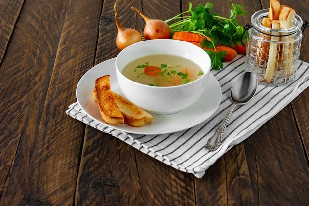 Caldo de galinha com salsa em uma tigela branca e croutons em um fundo de madeira rústico.