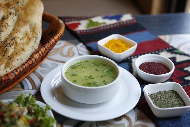 Caldo de galinha de vista lateral com especiarias e pão tandoor em uma cesta na mesa