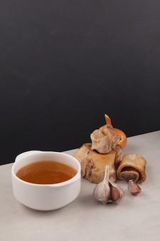 Caldo de osso de carne caseiro em uma tigela branca na mesa.