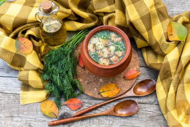 Caldo de outono em um prato de argila no fundo de um lenço amarelo