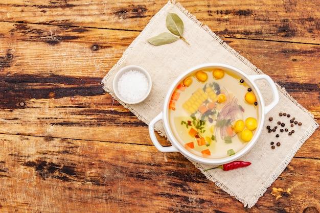 Caldo de pato transparente com bolinhos de massa e legumes