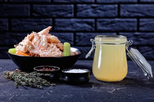 Caldo de peixe ou caldo de salmão em uma jarra de vidro sobre uma mesa de concreto com carne de peixe, ossos e vegetais em uma tigela ao fundo