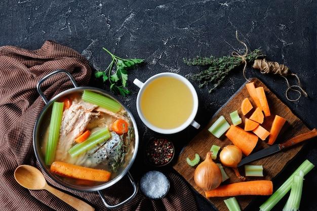 Caldo de peixe ou sopa de salmão, cebola, cenoura, aipo, ervas e especiarias em uma panela e em uma tigela branca sobre uma mesa de concreto
