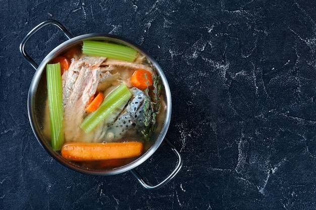 Caldo de peixe recém cozido de salmão, cebola, cenoura, talo de aipo e especiarias em uma panela em uma mesa de concreto