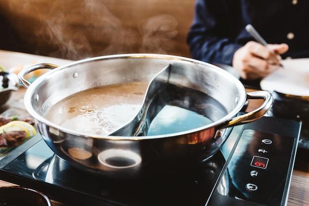 Caldo de shabu: base de sopa de shoyu e base de sopa clara em panela quente com vapor.