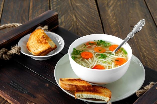 Caldo fresco em uma tigela branca com ervas picadas com salsa e alho sobre uma mesa de madeira. sopa quente feita com carne de frango, cenoura, cebola, alho, salsa e pimenta.