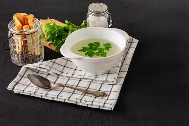 Caldo ou caldo de frango caseiro. café da manhã saudável. fundo de concreto preto