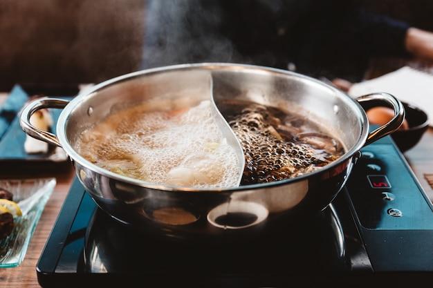 Caldo quente e ebuliente de shabu: base de sopa de shoyu e base de sopa clara em panela quente.