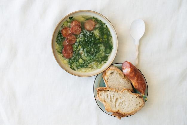 Caldo verde sopa com verduras e chouriço picado por cima em tigela de cerâmica com colher de cerâmica. pedaços de pão e chouriço no prato de cerâmica. vista do topo