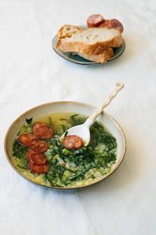 Caldo verde sopa com verduras e chouriço picado por cima em tigela de cerâmica com colher de cerâmica. pedaços de pão e chouriço no prato de cerâmica
