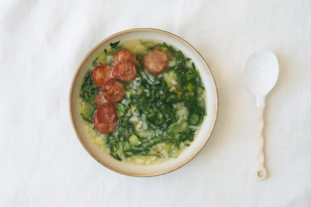 Caldo verde sopa com verduras e chouriço picado por cima em tigela de cerâmica com colher de cerâmica. vista do topo