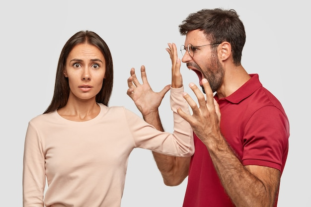 Cale-se! mulher bonita e intrigada mantendo a palma da mão perto da boca do marido