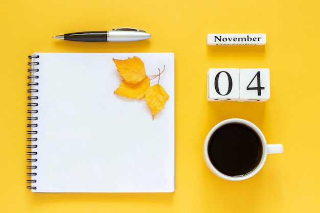 Calendário 04 de novembro xícara de café, bloco de notas com caneta e folha amarela em amarelo