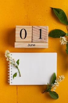 Calendário 1 de junho, caderno em branco para seu texto em uma superfície amarela com flores