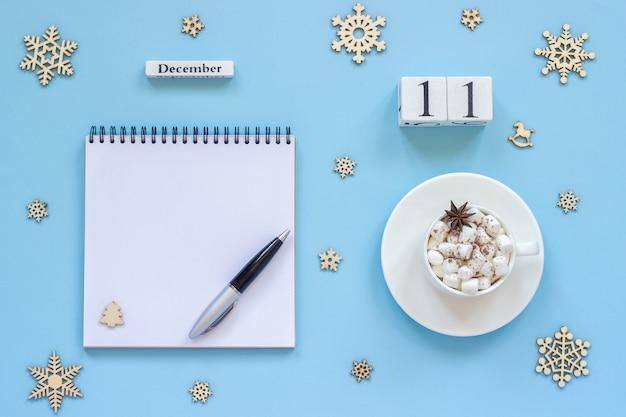 Calendário 11 de dezembro xícara de cacau e marshmallow, bloco de notas aberto vazio