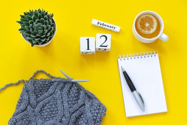 Calendário 12 de fevereiro. xícara de chá com limão, bloco de notas aberto vazio para texto