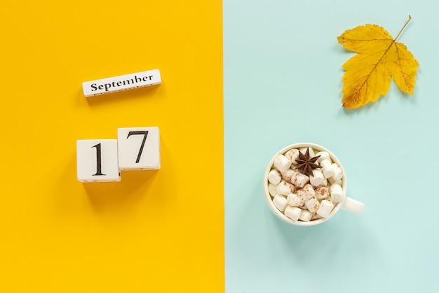 Calendário 17 de setembro, xícara de chocolate com marshmallows e folhas de outono amarelas sobre fundo azul amarelo